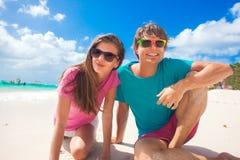 Пара с солнцезащитным кремом ставит точки на сторонах имея потеху на солнечном пляже Стоковые Фотографии RF