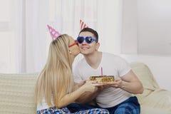 Пара с тортом с свечами поздравляет на его дне рождения дальше Стоковое Изображение
