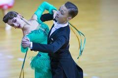 Пара танца Iliya Kochev и Alina Zhukovskaya выполняет программу стандарта Junior-2 Стоковые Изображения