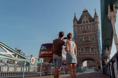 Пара фотографирует красный автобус двойной палуба на мосте башни в Лондоне стоковое изображение