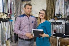 Пара человек и женщина, предприниматели малого семейного предприятия магазин Выставк-комнаты домашних тканей, тканей, занавесов стоковые фотографии rf