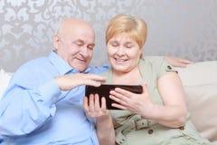 Пара читает книгу дома Стоковое Фото