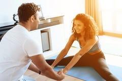 Пара Aframerican делая йогу работает дома Они сидят на поле на циновках для йоги Стоковое Изображение RF