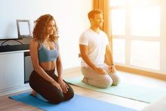 Пара Aframerican делая йогу работает дома Они сидят на поле на циновках для йоги Стоковые Изображения