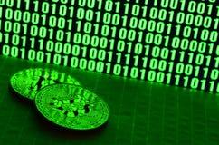 Пара bitcoins лежит на поверхности картона на предпосылке монитора показывая бинарный код ярких ых-зелен нулей и дальше Стоковые Фото