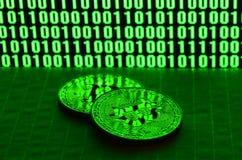 Пара bitcoins лежит на поверхности картона на предпосылке монитора показывая бинарный код ярких ых-зелен нулей и дальше Стоковые Изображения