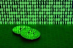 Пара bitcoins лежит на поверхности картона на предпосылке монитора показывая бинарный код ярких ых-зелен нулей и дальше Стоковые Изображения RF