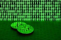 Пара bitcoins лежит на поверхности картона на предпосылке монитора показывая бинарный код ярких ых-зелен нулей и дальше Стоковая Фотография RF