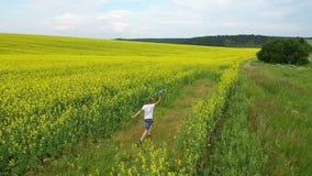 Парень бежит через поле цветка, держа самолет o акции видеоматериалы