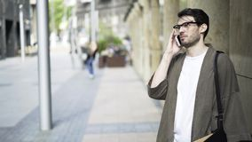 Парень битника в стеклах идя и говоря на телефоне снаружи сток-видео