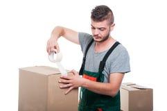 Парень движенца используя клейкая лента для герметизации трубопроводов отопления и вентиляции на картонной коробке Стоковые Фото