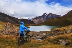 Парень в синем пиджаке с велосипедом На предпосылке высоких гор стоковое изображение rf