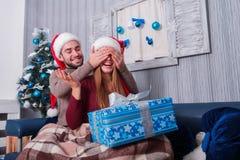 Парень делает девушкой сюрприз, закрывая ее глаза и представляя подарочную коробку Атмосфера рождества indoors стоковые фотографии rf
