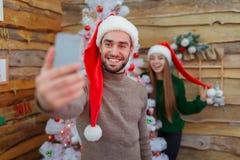Парень делает selfie на расплывчатой предпосылке девушки рядом с деревом стоковые фото
