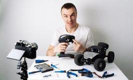 Парень держит видео- блог о контролируемых радио моделях автомобиля На таблице инструменты для ремонта стоковое фото rf
