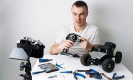 Парень держит видео- блог о контролируемых радио моделях автомобиля На таблице инструменты для ремонта стоковые фото
