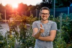 Парень детенышей усмехается и указывается палец на вас В парке на заходе солнца Стоковая Фотография RF