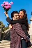 Парень девушки обнимая с цветками в руке. Стоковые Изображения