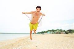 Парень летания имея потеху на пляже и имея полезного время работы Стоковая Фотография