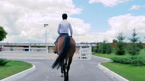 Парень едет на лошади к арене видеоматериал