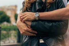 парень задний и обнимает девушку, руки совместно на руке вахты парня нося дата мужские руки, конец-вверх рук, обнимают стоковые изображения