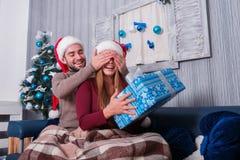 Парень закрывает глаза ` s девушки, пока девушка держит подарочную коробку рождества indoors стоковые фото