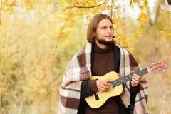 Парень играет на гавайской гитаре с небольшой улыбкой на его стороне стоковая фотография