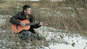 Парень играя гитару в природе сток-видео