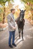 Парень идет с лошадью в парке осенью Стоковое Фото