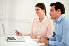 Парень и дама офиса смотря компьтер-книжку Стоковые Фото