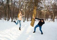 Парень и девушка бросают снежные комья на один другого в зиме снаружи стоковые фотографии rf