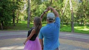 Парень и девушка в парке пробуют выполнить движение танца Переплетать вокруг Они имеют потеху и усмехаться сток-видео