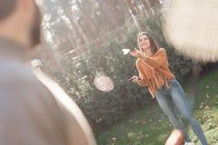 Парень и девушка играют бадминтон во время пикника с друзьями Стоковое Фото