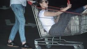 Парень и девушка имеют потеху в парковке Человек свертывает девушку в вагонетке от супермаркета в сток-видео