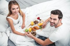 Парень и девушка имея завтрак в кровати стоковые фотографии rf
