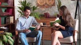Парень и девушка книги чтения пока сидящ в домашней библиотеке акции видеоматериалы