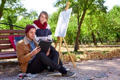Парень и девушка наблюдают изображения в их альбоме для рисовать стоковые изображения