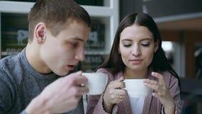 Парень и девушка сидят совместно в кафе Они выпивают чай Они влюбленн в один другого соедините влюбленность сток-видео
