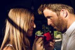Парень и девушка смотря один другого, и выпивая чашку чаю стоковое фото rf