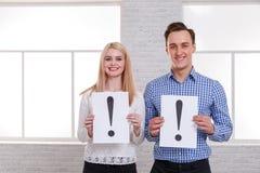 Парень и девушка с улыбкой держат листы с восклицательным знаком стоковое фото