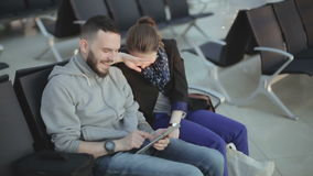 Парень и девушка в вскользь одежде смотрят экран и смеяться над таблетки сток-видео