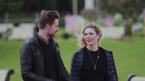 Парень и девушка идут в зону и беседовать парка милые друг с другом видеоматериал
