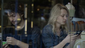 Парень и дистантная подруга осадки играя на smartphone имея проблемы и затруднения отношения сток-видео