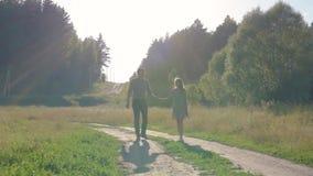 Парень и подруга, любящая пара идя и целуя на заходе солнца в сельских mestres на природе сток-видео