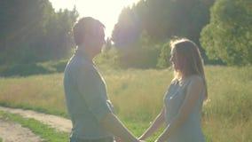 Парень и подруга, любящая пара идя и целуя на заходе солнца в сельских mestres на природе видеоматериал