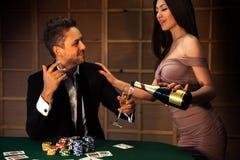 Парень красоты flirting с девушкой которая льет шампанское на покере Стоковое фото RF