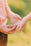 Парень кладя обручальное кольцо в его палец подруги outdoors, конец-вверх Стоковое Изображение RF