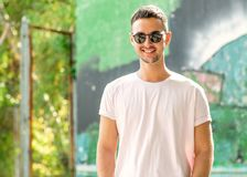 Парень моды представляя outdoors в солнечных очках стоковое изображение