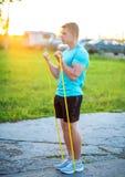 Парень нагнетает мышцы бицепса в совместных учениях вечера Образ жизни лета, мотивировка сильн Человек внутри стоковое изображение