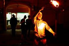 Парень на улице выполняет с факелами огня Стоковые Фотографии RF